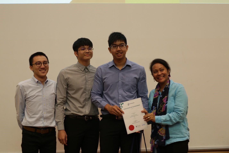 Tengku Nasariah awarding Petrosain's certificate to the winning team, Team 'Drop the Stick'.